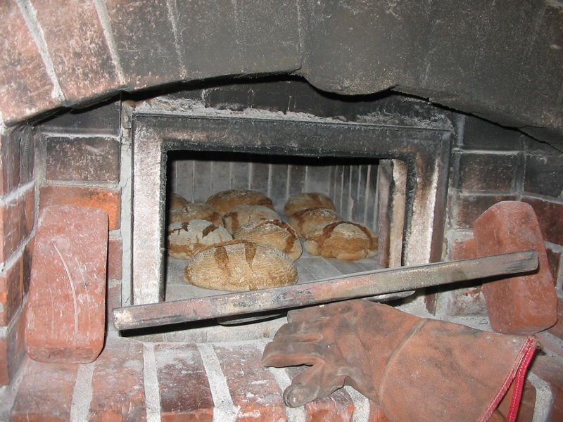 Bread ready to come out of Brian Thomas\' wood-fired oven.