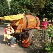 My friend Ellery, pictured at right, at a Kvass wagon in Lithuania. The cart was busy as hell, and people were filling up empty soda bottles, glass jars, and thin plastic cups. It was about 5 cents a cup.