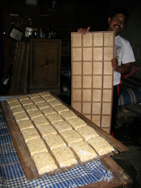 Releasing shaped tempeh blocks in bags onto bamboo racks.
