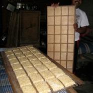 Releasing shaped tempeh blocks in bags onto bamboo racks.