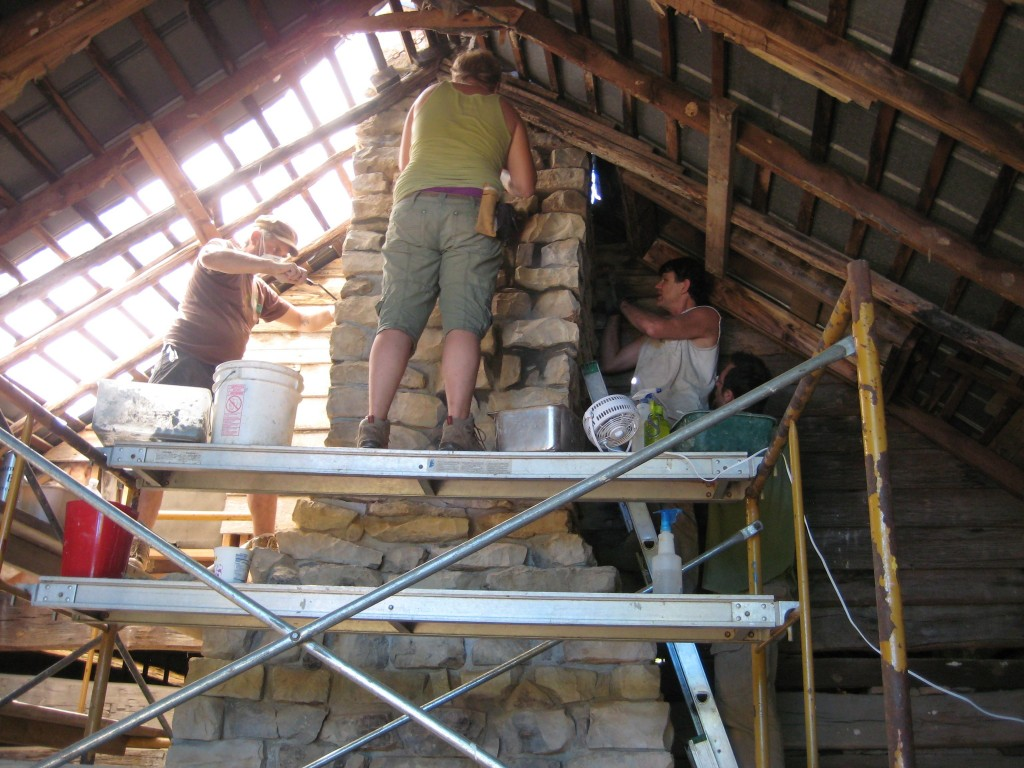 Repointing the chimney. Leopard, Fish, and Tom approach the roofline, as masonry mentor Willy advises.