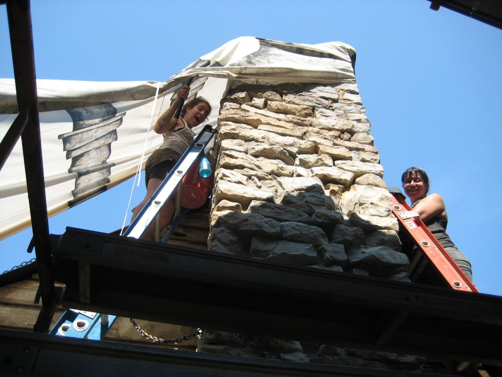Sarah and Josefina repointing above the roofline.