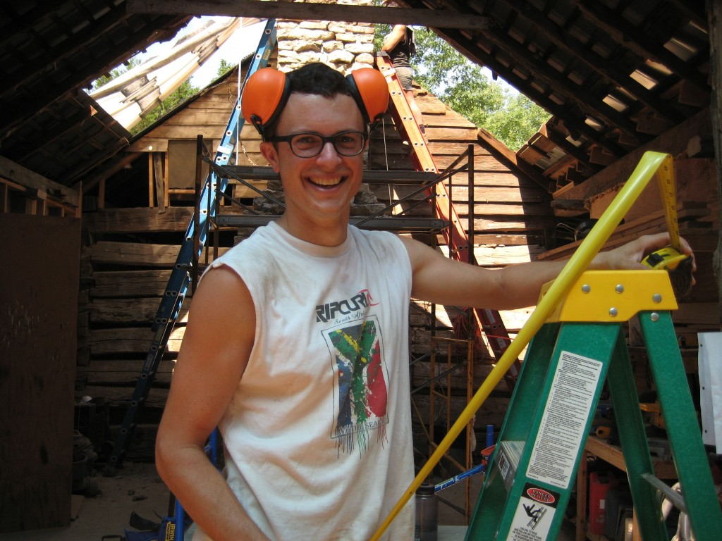 Gabriel checking measurements for a rafter cut, while wearing ear protection in the style of the Mouseketeers.