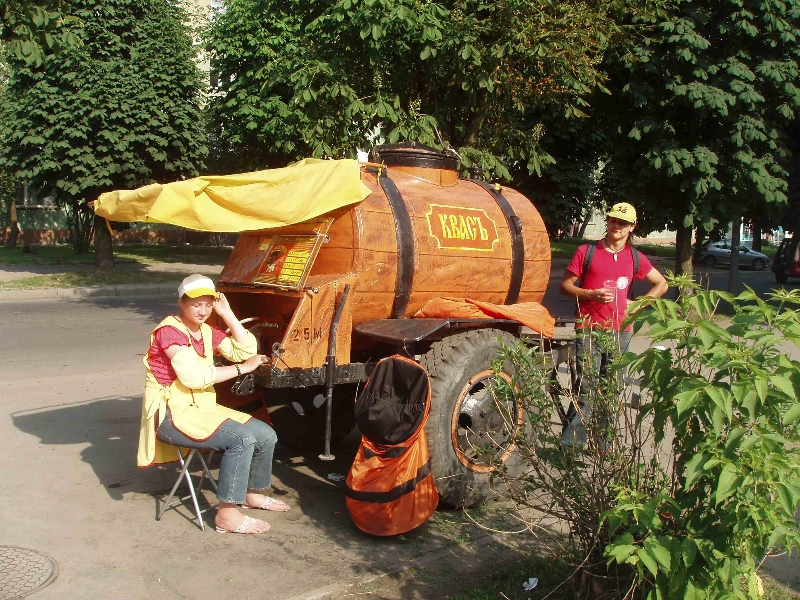 "My friend Ellery, pictured at right, at a Kvass wagon in Lithuania. ""The cart was busy as hell, and people were filling up empty soda bottles, glass jars, and thin plastic cups. It was about 5 cents a cup."""